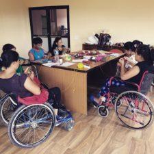 Fem af Himmellegs medarbejdere sidder og strikker og hækler bæredygtigt legetøj i deres kørestole